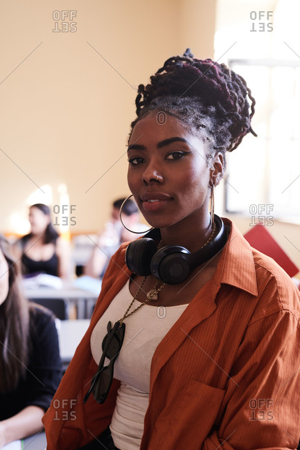 Portrait of confident female student with headphones in classroom