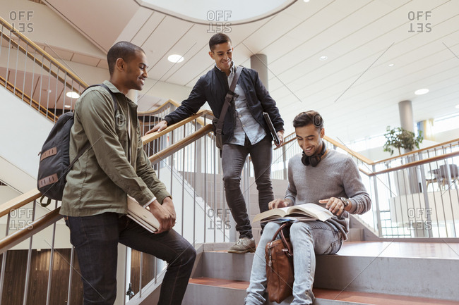 Smiling male friends discussing over book on steps in university