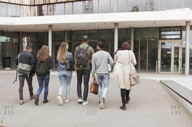Rear view of multi-ethnic students walking against building in high school campus