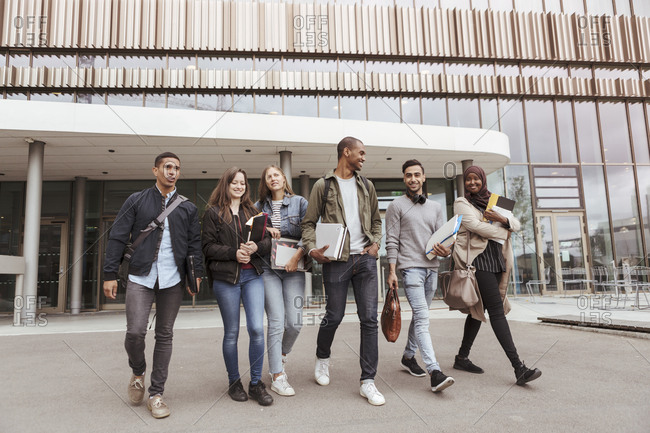 Full length of multi-ethnic university students walking against building in campus