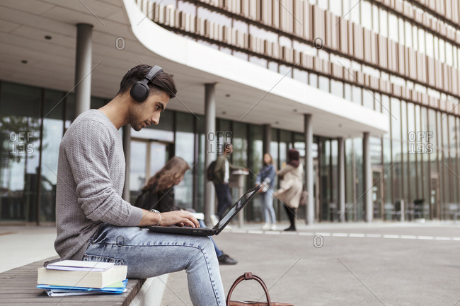 Young student listening music while using laptop at university campus