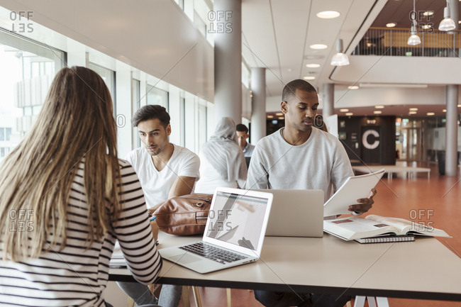 Multi-ethnic students studying together while sitting in university cafeteria