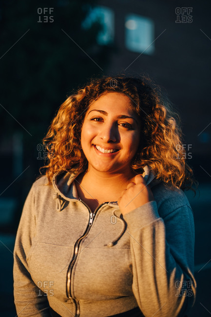 Portrait of smiling young woman in hooded shirt at sunset