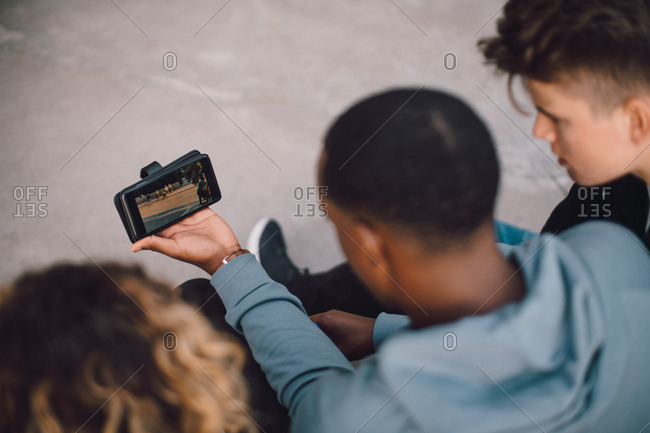 High angle view of male and female friends watching movie on smart phone