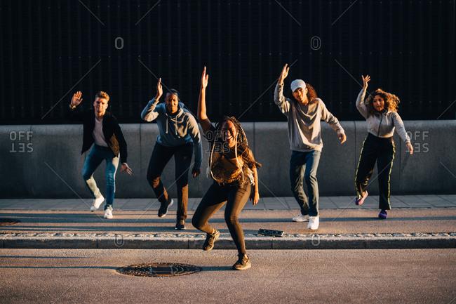 Full length of multi-ethnic friends dancing on sidewalk in city