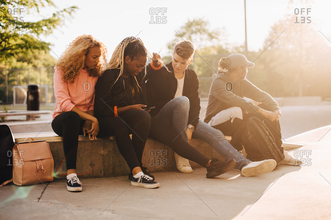 Multi-ethnic friends looking at smart phone while sitting at skateboard park
