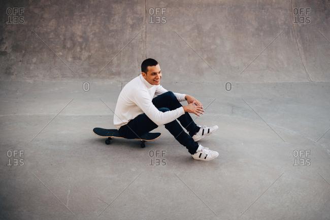 Full length of smiling man sitting on skateboard at park