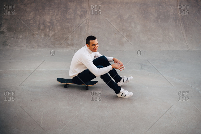 Full length of smiling man sitting on skateboard at park