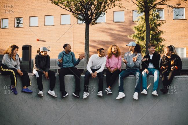Full length of multi-ethnic friends sitting at skateboard park