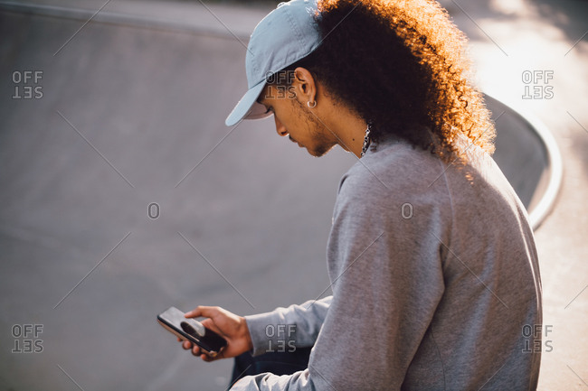 Young man text messaging on smart phone at skateboard park