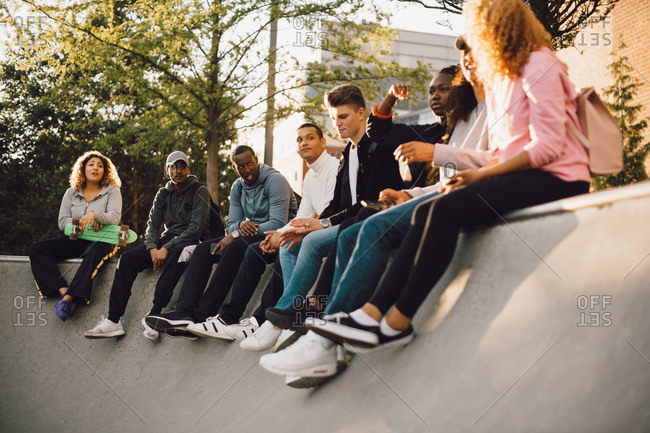 Multi-ethnic friends sitting at skateboard park