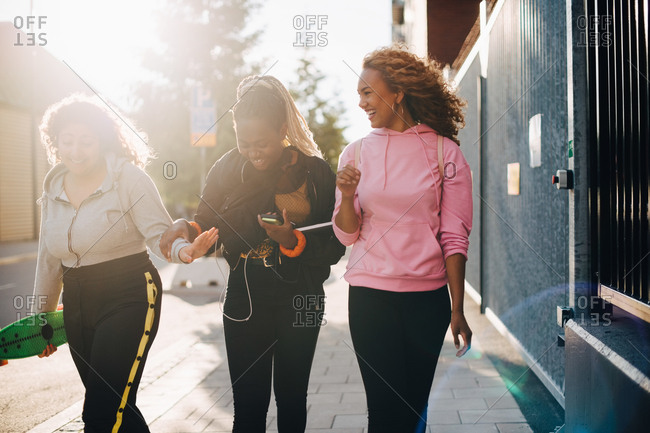 Smiling female friends talking while walking on sidewalk in city
