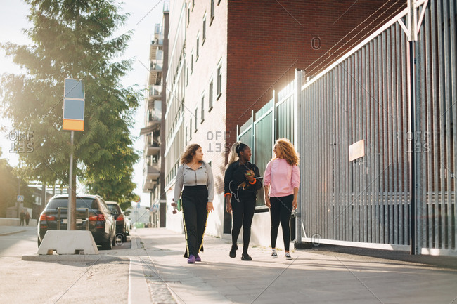Full length of friends talking while walking on sidewalk in city