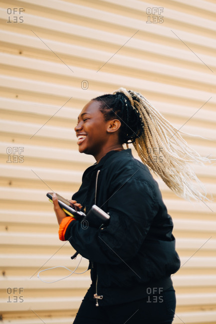 Laughing teenage girl holding smart phone while walking by shutter in city