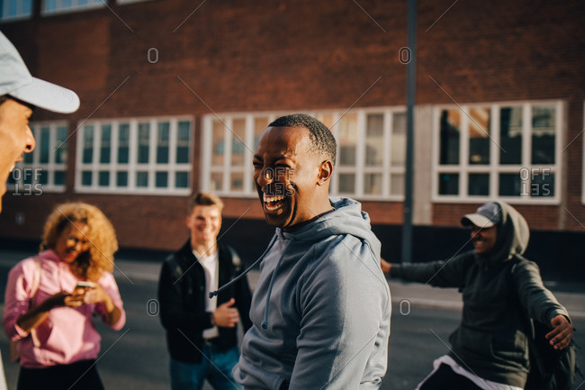 Cheerful young man dancing with friends in city on sunny day