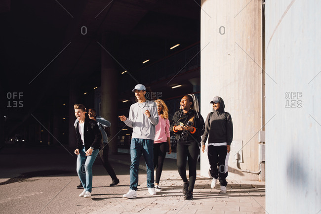 Happy friends looking away while walking on street under overpass in city during sunny day