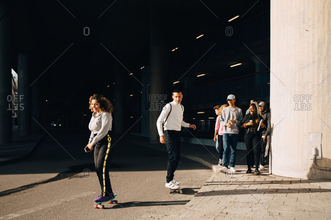 Friends looking at man and woman skateboarding on road during sunny day