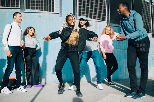Smiling friends looking at teenage girl dancing on sidewalk in city