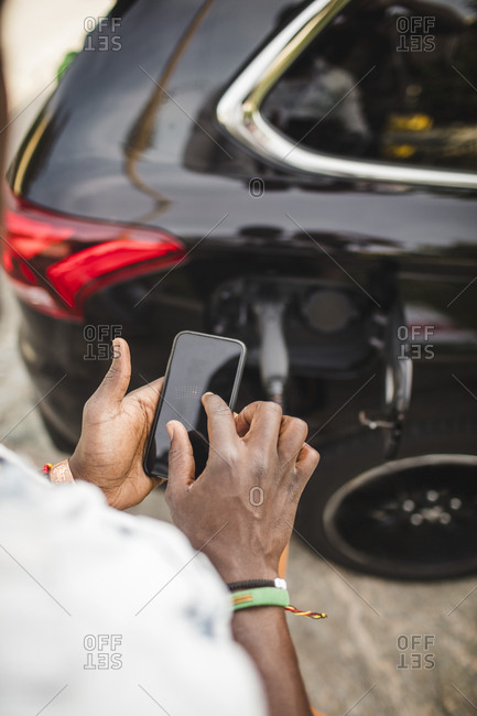 Cropped image of man using smart phone while standing by car on driveway
