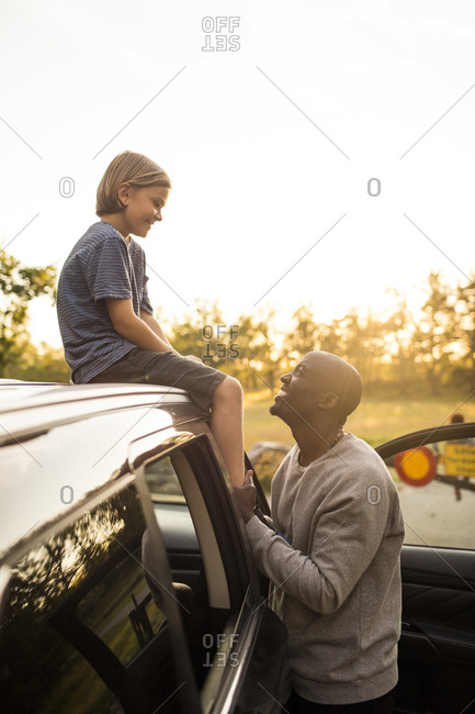 Smiling man looking at girl sitting on car roof during sunset at park