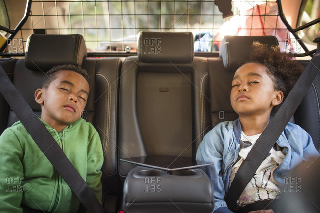 Tired siblings sleeping in electric car