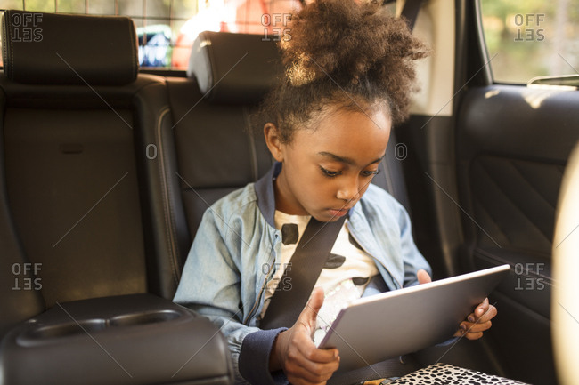 Girl using digital tablet while sitting in electric car