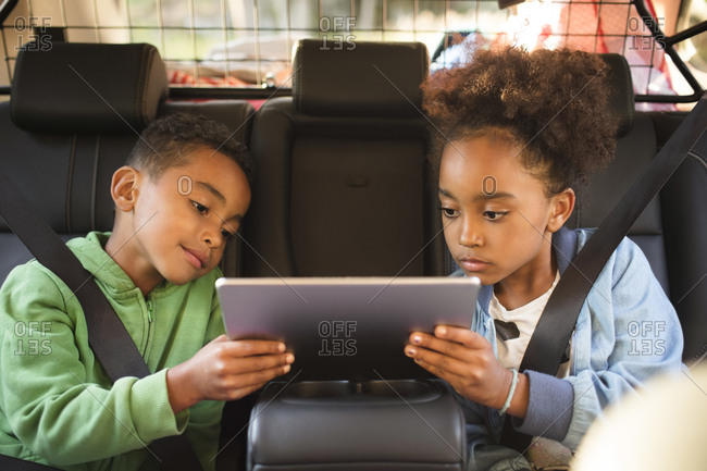 Siblings sharing digital tablet while sitting in electric car