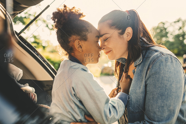 Smiling woman and daughter sitting face to face with eyes closed in car trunk during picnic