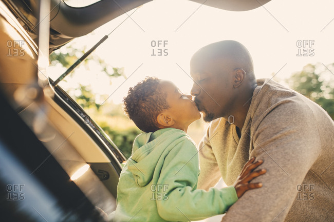 Father kissing son sitting in car trunk