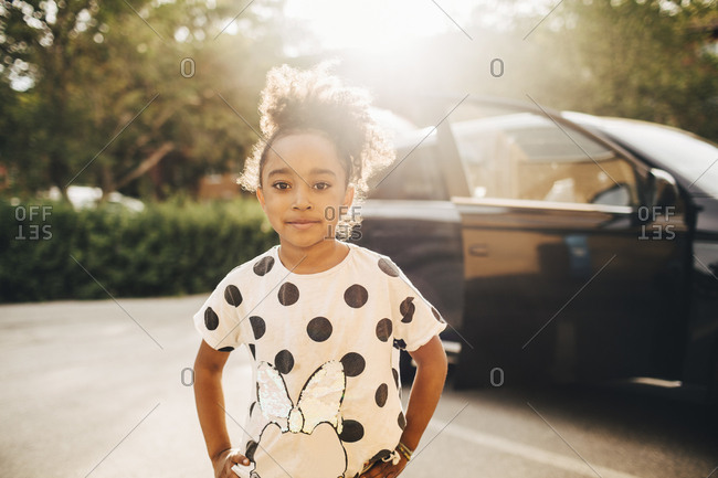 Portrait of girl standing against electric car on driveway