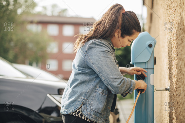 Side view of woman adjusting electric plug for charging car at station