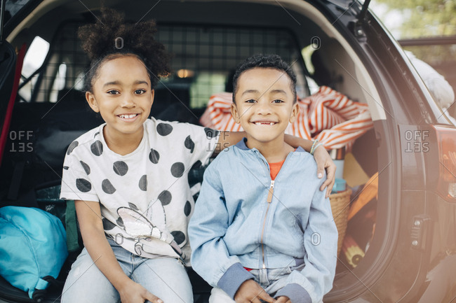 Portrait of smiling girl sitting with arm around on brother in electric car trunk