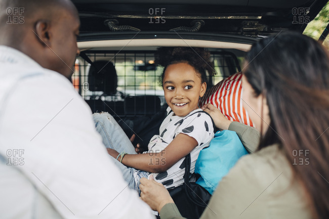 Smiling girl looking at mother standing by father while sitting on luggage in car trunk