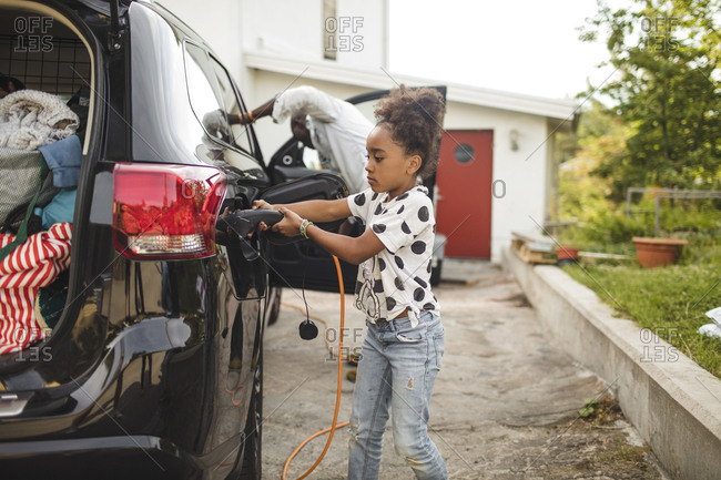 Girl charging electric car while standing on driveway