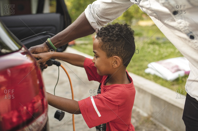 Midsection of man assisting son in charging electric car on driveway at front yard