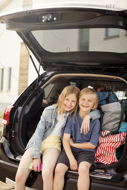 Portrait of smiling siblings sitting in car trunk against house