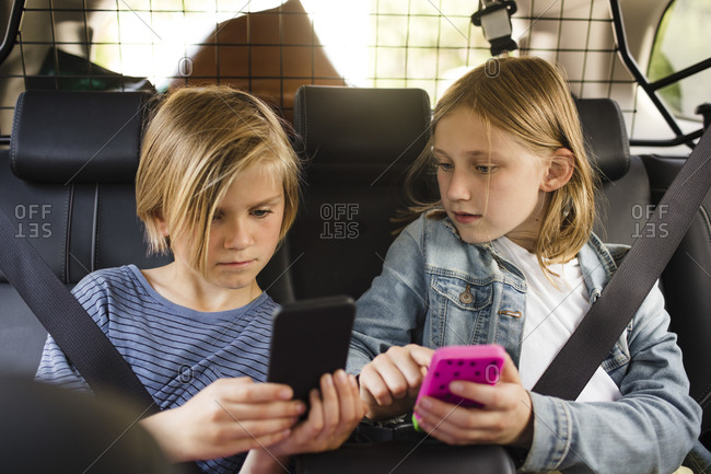 Blond siblings using smart phones while sitting in car