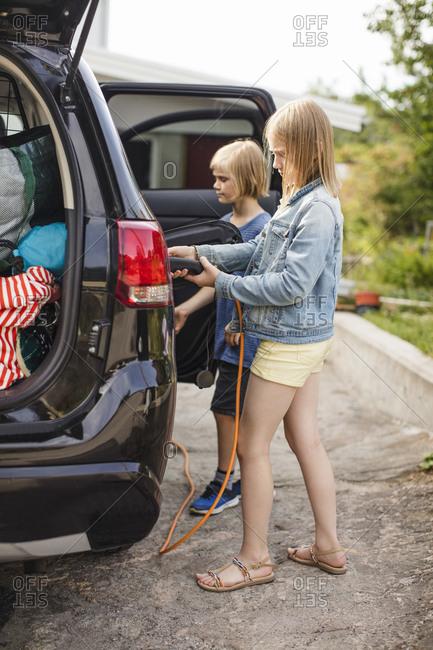 Full length of siblings charging electric car on driveway