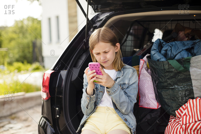 Blond girl using smart phone while sitting in electric car trunk
