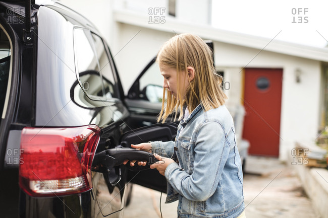 Side view of blond girl charging electric car in driveway