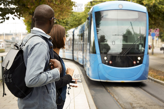 Commuters waiting on sidewalk while looking at blue tram in city