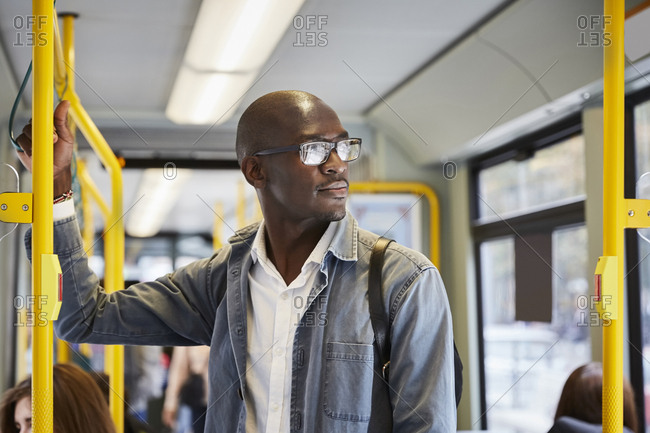 Confident male commuter looking away while standing in tram
