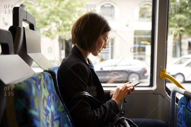 Side view of businesswoman using smart phone while sitting in bus