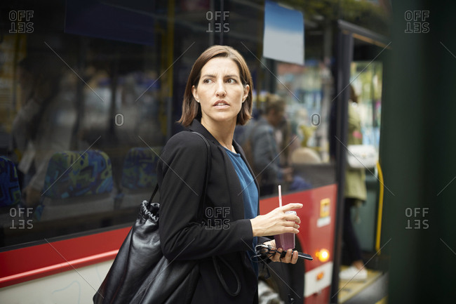 Confident businesswoman looking away while standing with drink against bus in city