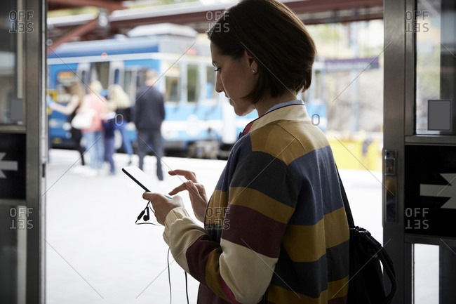 Businesswoman using smart phone while standing in railroad station