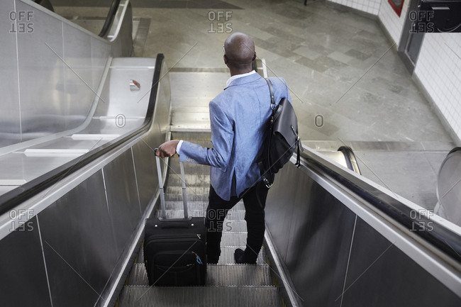 High angle rear view of businessman standing with luggage on escalator at subway station