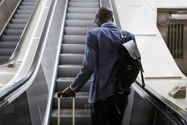 Rear view of businessman standing with luggage moving up on escalator at subway station