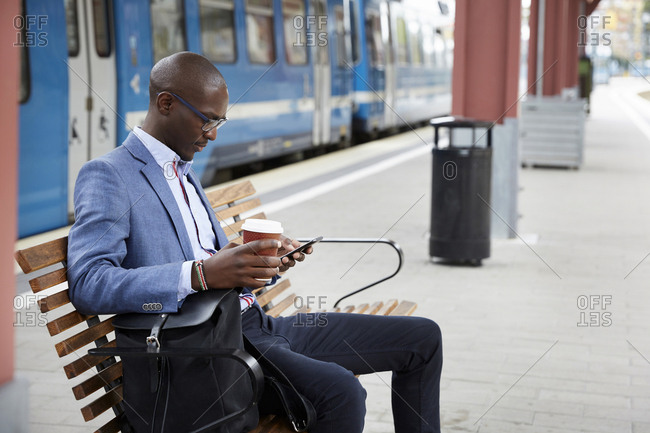 Businessman using smart phone while sitting with coffee at railroad station