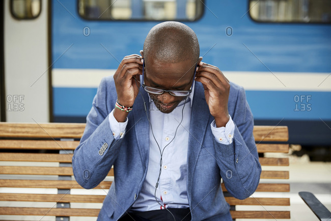 Businessman adjusting in-ear headphones while sitting at railroad station