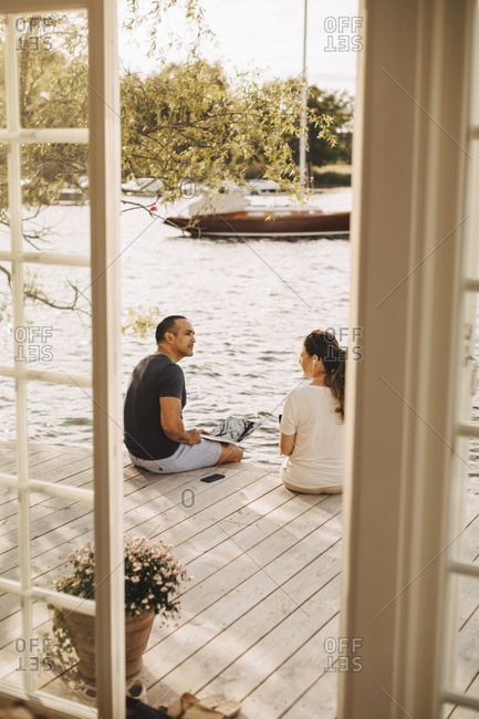 Mature couple talking while working at patio seen through open door of holiday villa